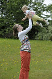 Mother throwing her baby in the air,outdoors Stock Image