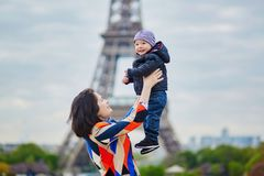 Mother throwing her little son in the air near the Eiffel tower Stock Photo