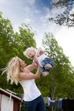 Mother Throwing Son in Air Royalty Free Stock Photography