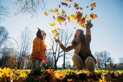 Mother throws autumn leaves on daughter in the park Royalty Free Stock Images