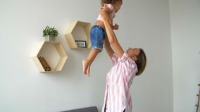 Excited young mother and child playing on the couch. Mother throws baby into the air. Mother throws baby into the air. Smiling mom with child having fun enjoy stock footage