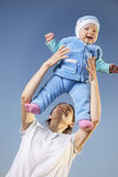 Mother throws baby on blue beckground stock images