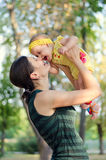 Mother throws her daughter. Mom throws up and kisses her daughter in the Park royalty free stock photo