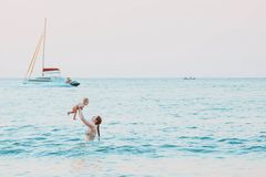 Mother throws up baby in the sky in water of the sea. Happy family summer leisure with infant girl. Yacht and hydrocycle on. Background stock photos