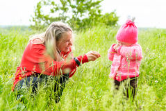 Mother tickles daughter blade of grass in the tall grass Stock Photography