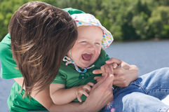 Mother tickling child. Young mother playing and tickling laughing daughter Royalty Free Stock Image