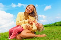 Mother tickling funny baby son lying on her laps. Happy family on green grass lawn. Child have fun on outside walk - mother tickling funny baby son lying on her Royalty Free Stock Images