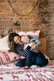 Mother is tickling her son, happy family have fun at bed on living room. Christmas morning, festive mood royalty free stock photography