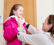 Mother ties her daugher a scarf Stock Photo