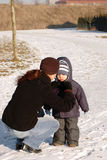 Mother ties  a scarf on the child. Royalty Free Stock Photo