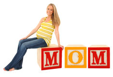 Mother to Be. Sitting on alphabet block word mom Royalty Free Stock Photo