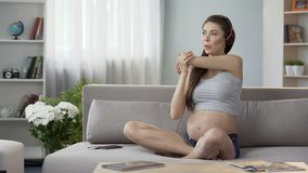 Mother-to-be in headphones sitting, stretching upper body, breathing technique. Stock footage stock video footage