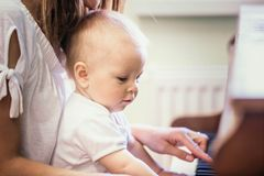 Mother and toddler baby boy, playing piano at home royalty free stock image
