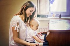 Mother and toddler baby boy, playing piano at home Stock Photos