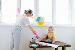 Mother of a toddler boy is cleaning plastic window door with wet cloth. Mother of little blond toddler boy is cleaning plastic window door with wet cloth. He royalty free stock photos