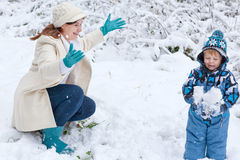 Mother and toddler boy having fun with snow Royalty Free Stock Photos