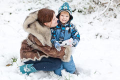 Mother and toddler boy having fun with snow Royalty Free Stock Images
