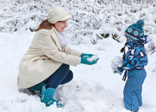 Mother and toddler boy having fun with snow Stock Photos