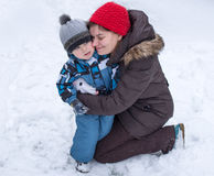 Mother and toddler boy having fun with snow on winter day Royalty Free Stock Image