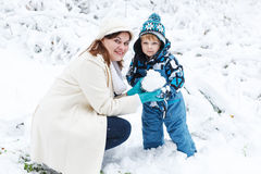 Mother and toddler boy having fun with snow on winter day Stock Images