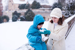 Mother and toddler boy having fun with snow on winter day Royalty Free Stock Photo