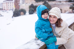 Mother and toddler boy having fun with snow on winter day Royalty Free Stock Photos