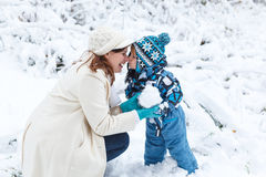Mother and toddler boy having fun with snow on winter day Royalty Free Stock Photography
