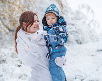 Mother and toddler boy having fun with snow on winter day Stock Photo