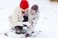 Mother and toddler boy having fun with snow on winter day Stock Image