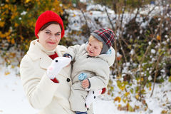Mother and toddler boy having fun with snow on winter day Stock Photos