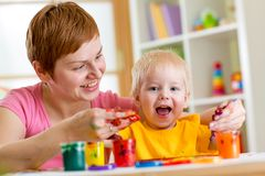 Mother and toddler boy paint together at home Royalty Free Stock Photos