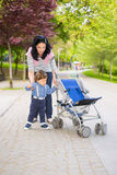 Mother and toddler boy pushing pram. Mother helping toddler boy to pushing  his pram in park Royalty Free Stock Images