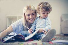 Mother and toddler boy spending time together. Inside living room Royalty Free Stock Photos