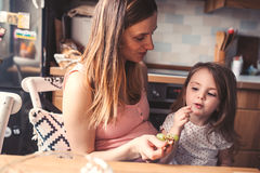 Mother and toddler daughter eating grapes for breakfast at home Stock Images