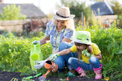Mother and toddler daughter gardening and watering Royalty Free Stock Photos