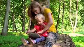 Mother with toddler daughter girl using tablet computer sit on fallen tree trunk stock footage