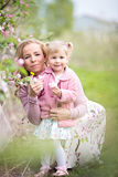 Mother and toddler daughter holding apple tree flowers in orchar Stock Image
