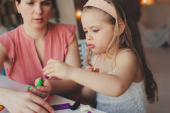 Mother and toddler daughter playing with plasticine or play dough at home. Stock Photography