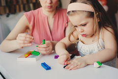Mother and toddler daughter playing with plasticine or play dough at home. Stock Images