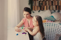 Mother and toddler daughter playing with plasticine or play dough at home. Stock Photo
