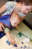 Mother with toddler drawing picture. Mother with toddler drawing a picture on a cardboard at home Royalty Free Stock Photography