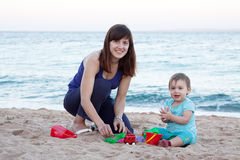 Mother with  toddler plays on  beach Stock Photos