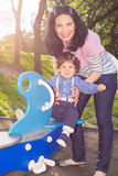 Mother and toddler on seesaw in sunbeam Royalty Free Stock Image