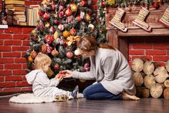 Mother and toddler son holding Christmas ball. On Christmas tree at home royalty free stock photography