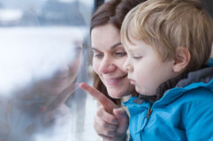 Mother and toddler son looking out train window outside. Happy mother and toddler son looking out train window outside, while it moving. travel Royalty Free Stock Photos