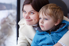 Mother and toddler son looking out train window outside Stock Images