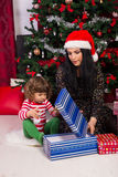 Mother and toddler son open Christmas gift Royalty Free Stock Image