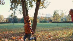 Mother and toddler son are playing together with fallen leaves in the autumn park or forest. Mom is throwing leaves in stock footage