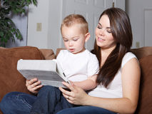 Mother and toddler son reading from wireless tablet Royalty Free Stock Photography