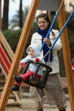 Mother with  toddler on swings Stock Photo